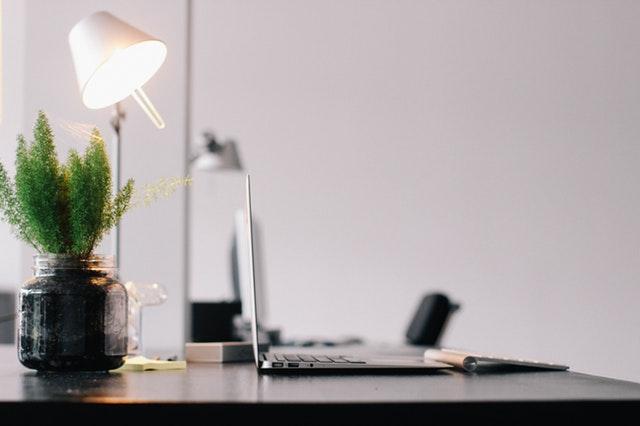 stůl s notebookem a lampičkou